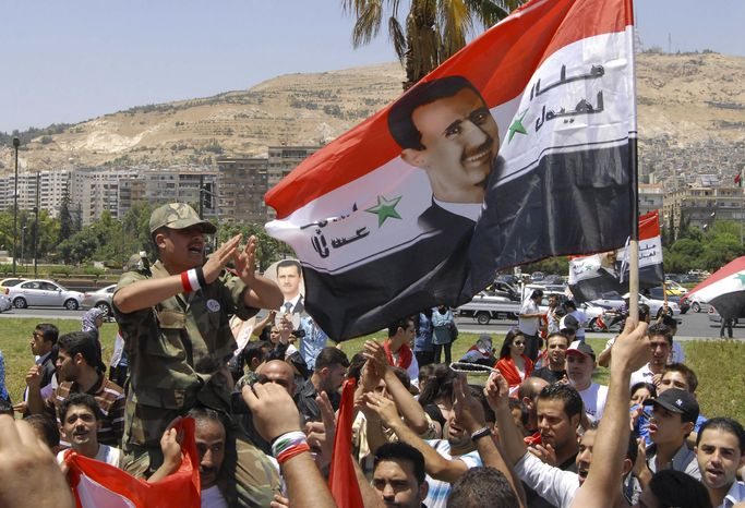 Demonstrators shout slogans in support of Syrian President Bashar Assad in Damascus, Syria, on Monday, June 20, 2011. (AP Photo/Muzaffar Salman)