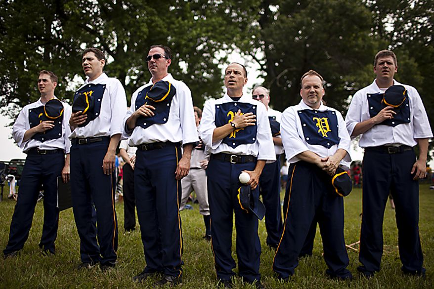 The Potomac Nine hold their hats over their hearts during the National Anthem before the game against the Elkton Eclipse during the Loudoun Preservation Society's 19th Century Baseball Day at the Oatlands, in Leesburg, Va., Sunday, June 12, 2011. Unlike today's game, the umpire instructed fans and players to all sing in unison, instead of just one person singing at the start.  (Drew Angerer/The Washington Times)