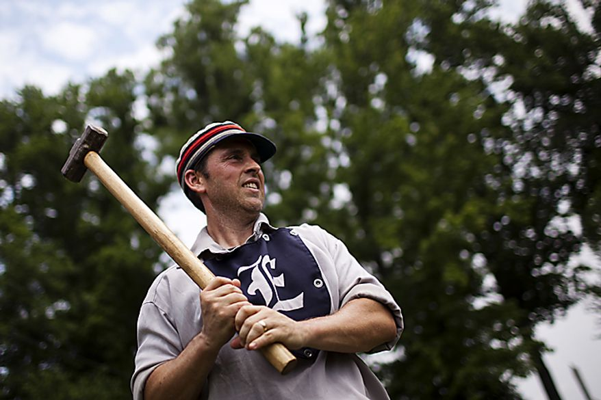 "Elkton Eclipse catcher Tim ""Ones"" Bower, of Rising Sun, Md., warms up on deck with a ""hammer"" weighted bat during the Loudoun Preservation Society's 19th Century Baseball Day at the Oatlands, in Leesburg, Va., Sunday, June 12, 2011. ""It doesn't really help me warm up and it's probably messing up my swing, but it's what they used to use."" (Drew Angerer/The Washington Times)"