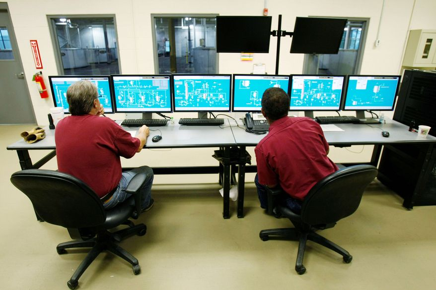 Wild Turkey workers Steve Crossfield (left) and Ronald Harvey monitor the computerized processing of bourbon in the control room of the new facility in Lawrenceburg, Ky. Wild Turkey can produce twice as much bourbon since the upgrade. (Associated Press)