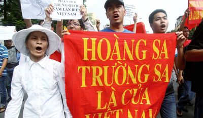 "Vietnamese protesters carry a banner with a slogan saying, ""Paracel Islands and Spratly Islands belong to Vietnam,"" in Hanoi earlier this month. Protesters tell China to stay out of their waters after Beijing's increased activities around disputed areas. (Associated Press)"