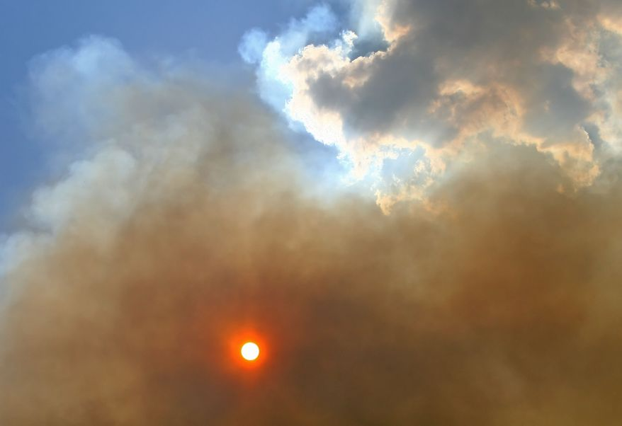 The sun shines through wildfire smoke on Monday, June 20, 2011, in Grimes County near Plantersville, Texas. (AP Photo/The Courier, Karl Anderson)