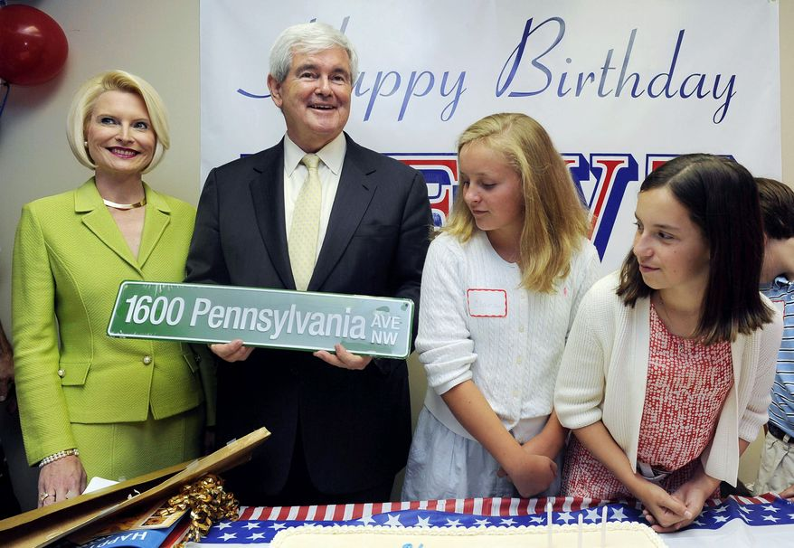 ASSOCIATED PRESS  Republican presidential candidate Newt Gingrich holds one of his presents, a road sign with the White House address on it, as wife Callista (left), granddaughter Maggie Cushman, 11, (right) and Clara Hunter look on during his 68th birthday party on Wednesday. Mr. Gingrich said political consultants find his ways difficult.