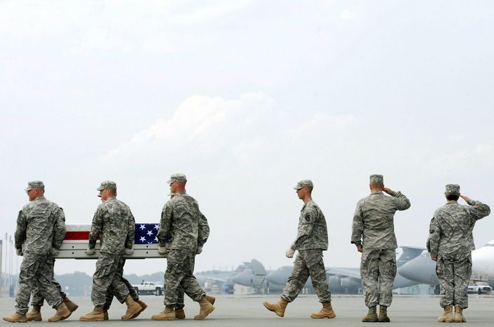 """ASSOCIATED PRESS SACRIFICE: Army soldiers carry a casket containing the remains of Sgt. James W. Harvey II on Wednesday at Dover Air Force Base in Delaware. The remainder of the 33,000 troop """"surge"""" that President Obama ordered to Afghanistan in December 2009 will be withdrawn before September 2012."""