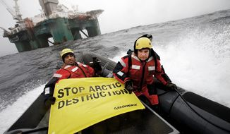 Greenpeace International global chief Kumi Naidoo (left) and an unidentified acquaintance make their view known on a boat near an oil rig in the Davis Strait, off Greenland's west coast, on Friday. Greenpeace said Mr. Naidoo was making a third attempt to stop a Scottish oil company from deep-water drilling in Arctic waters. (Associated Press)