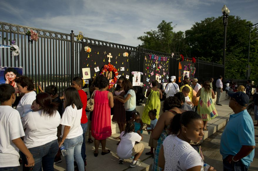 Family and friends of some of the crash victims spend time at a personal, makeshift memorial on The Charles A. Langley Bridge near the Fort Totten Metro Station in Washington, D.C. (Rod Lamkey Jr./The Washington Times)