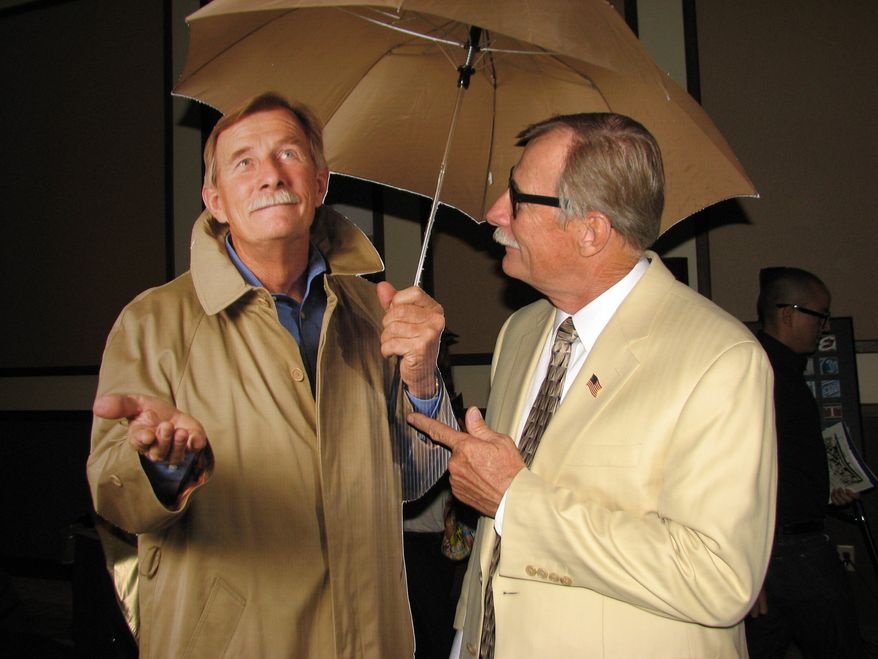 Yuma Mayor Al Krieger stands by a life-size cutout of himself in Yuma, Ariz., on June 16, 2011. When placed in hotel lobbies, the cutout of the mayor wearing a raincoat and toting an umbrella will signal an official cloudy day, triggering Code Gloom, a promotion that will offer hotel guests free meals on sunless days. (AP Photo/Yuma Sun, Mara Knaub)