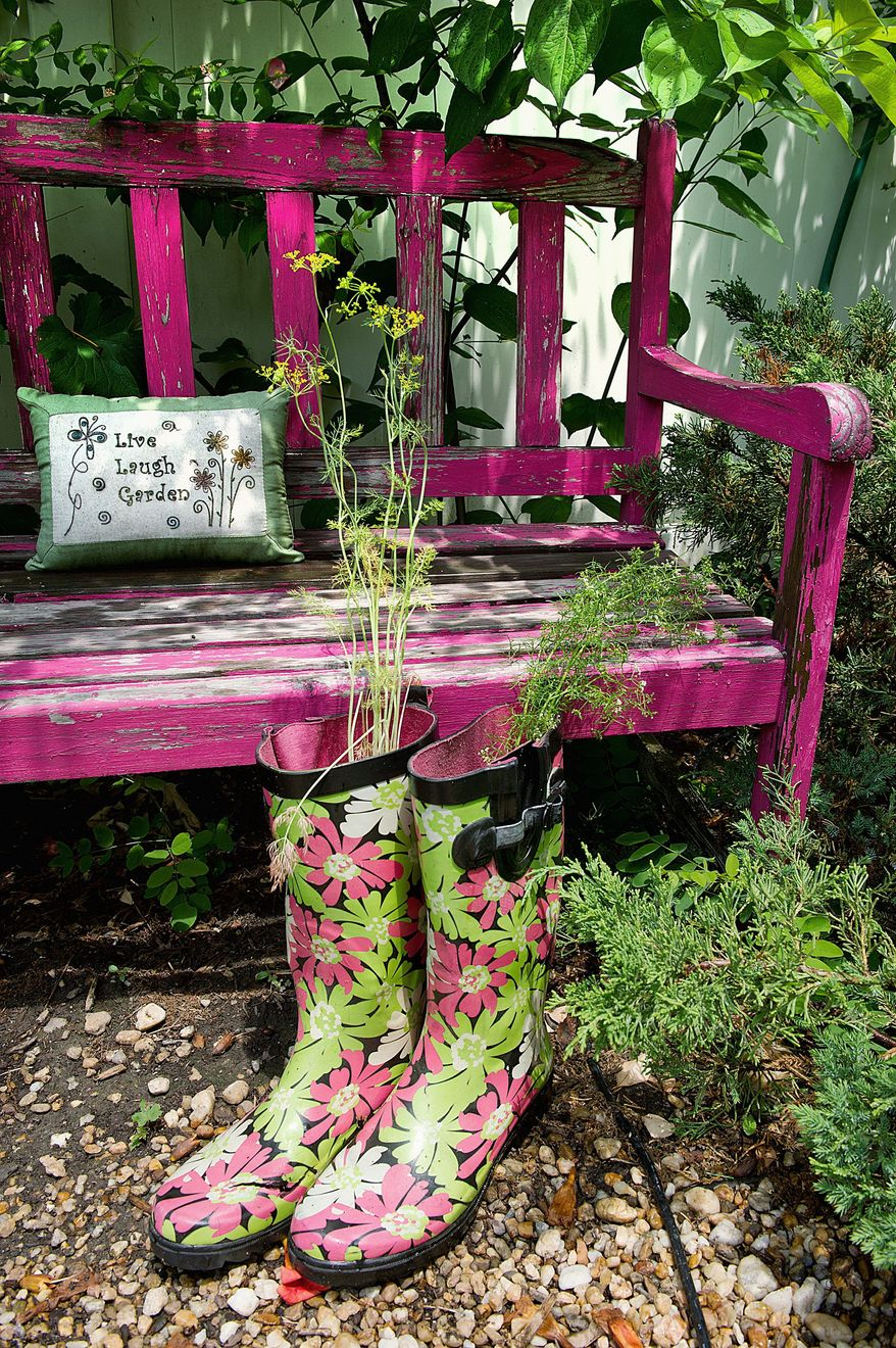 Part of making her cottage garden homier is adding touches like this bench, a pillow, and using patterned boots as a planter for Silver Spring, Md., gardener Kathy Jentz, who is also editor of Washington Gardener magazine. This image was made Monday, June 20, 2011. (Barbara L. Salisbury/The Washington Times)