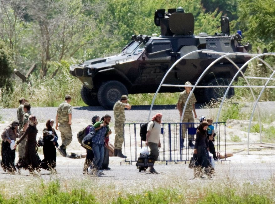 ASSOCIATED PRESS Syrian refugees forced north by a crackdown on protesters pass a Turkish military vehicle as they cross the border near Guvecci, Turkey, on Thursday.