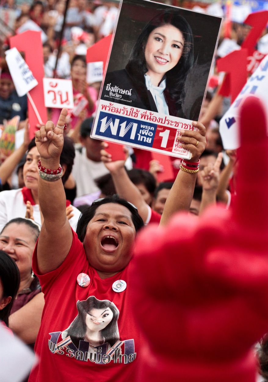 ASSOCIATED PRESS Supporters of Thai prime minister candidate Yingluck Shinawatra cheer her arrival during a rally in Bangkok. She is in a tight race with incumbent Abhisit Vejjajiva, who has been in power for 30 months. The nation's voters go to the polls on July 3.