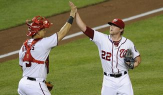 Washington Nationals relief pitcher Drew Storen (22) celebrates the 2-1 win over the Seattle Mariners with catcher Wilson Ramos (3) during a game Wednesday night. (AP Photo/Nick Wass)