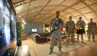 Spc. Gavin Fruge, 22, of Crowley, La., left, watches a rebroadcast of President Barack Obama's speech on proposed troop withdrawal with fellow soldiers at Kandahar Airfield Thursday, June 23, 2011, in Kandahar, Afghanistan. (AP Photo/David Goldman)