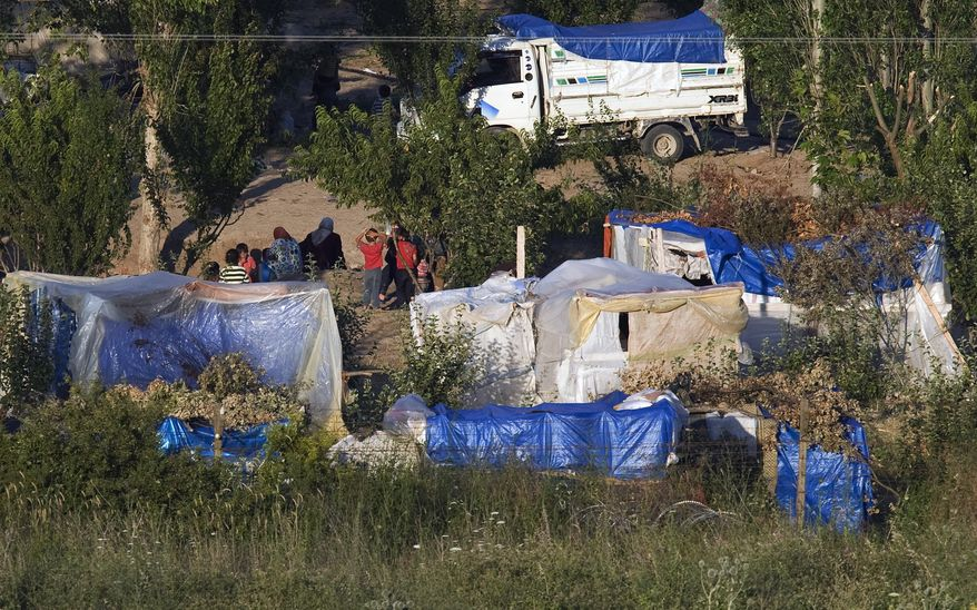 Syrians living in makeshift tents inside Syria near the Turkish border village of Guvecci are seen shortly before Turkey's Red Cresdent distribute free food alongside Turkey-Syria border near the Turkish village of Guvecci in Hatay province, Turkey, on June 22, 2011. (Associated Press)