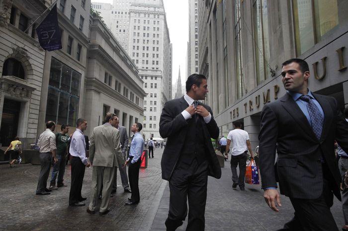 Businessmen walk June 23, 2011, on Wall Street in New York. (Associated Press)