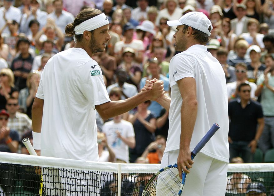 Spain's Feliciano Lopez, left, shakes hands after defeating Andy Roddick of the US in their match at the All England Lawn Tennis Championships at Wimbledon, Friday, June 24, 2011. (AP Photo/Alastair Grant)
