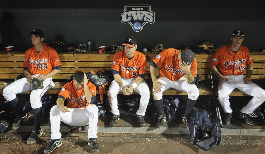 Virginia players sit in the dugout after losing 3-2 to South Carolina in 13 innings in an NCAA College World Series baseball game in Omaha, Neb., Friday, June 24, 2011. South Carolina advances to the championship series. (AP Photo/Dave Weaver)