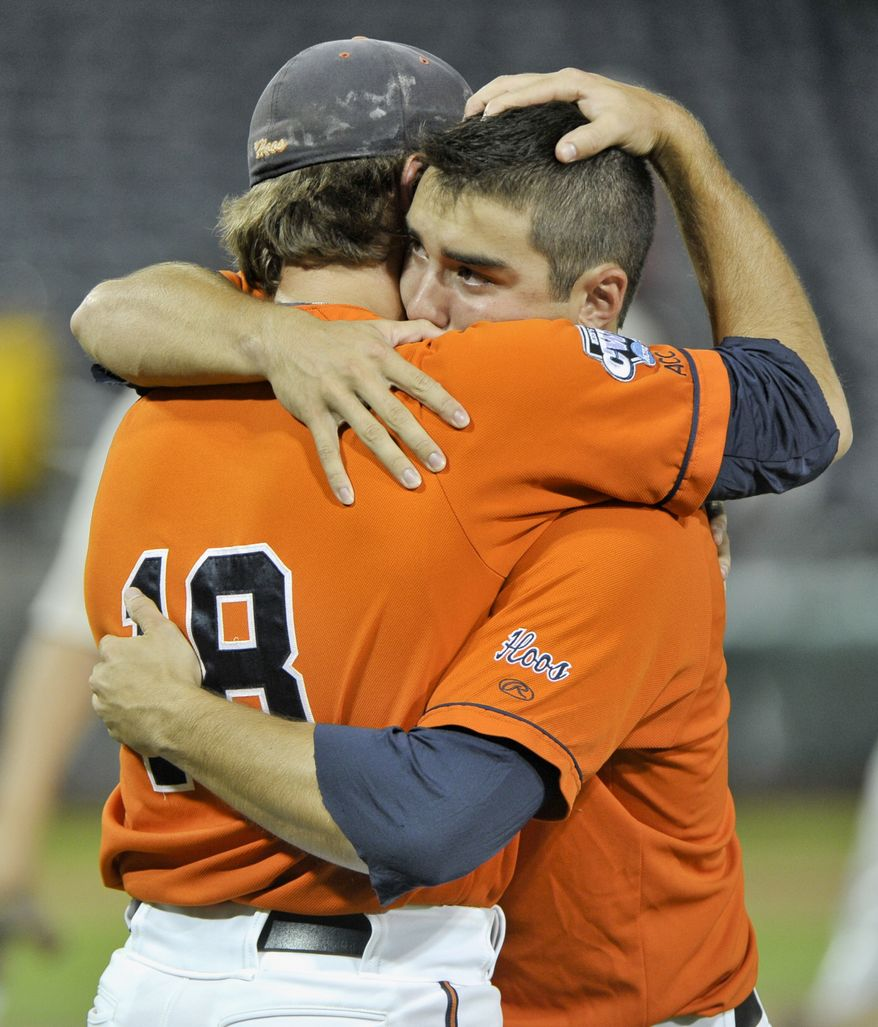 Virginia's Tyler Wilson, left, and Colin Harrington hug after losing to South Carolina in an NCAA College World Series baseball game in Omaha, Neb., Friday, June 24, 2011. South Carolina beat Virginia 3-2 in 13 innings and advances to the championship series. (AP Photo/Ted Kirk)