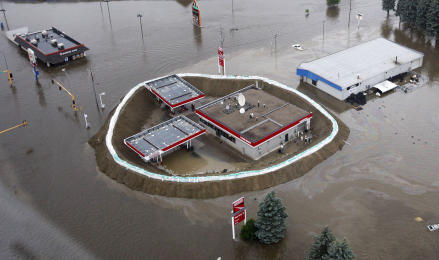 In this aerial photo, a Conoco gas station is surrounded by sand bags, the flood waters of the Souris River and an oil slick Friday, June 24, 2011, in Minot, N.D. North Dakota Gov. Jack Dalrymple says the Souris River is flowing over most levees in Minot as it surges past a 130-year-old record level. (AP Photo/Charles Rex Arbogast)