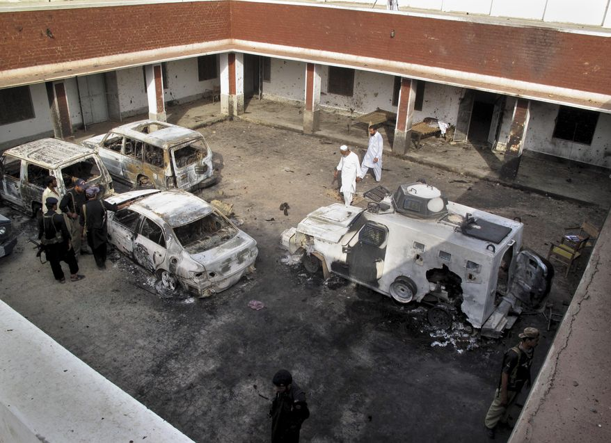 Police in Kolachi, Pakistan, near Dera Ismail Khan, examine damaged vehicles on Sunday, June 26, 2011, a day after Taliban husband-and-wife suicide bombers attacked the police station. (AP Photo/Kashif Naveed)
