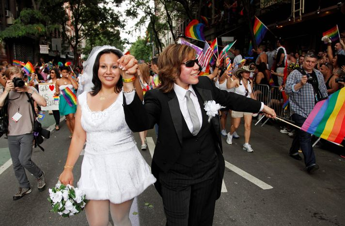 ** FILE ** Paola Perez, left, and her partner Linda Collazo, march in the Gay Pride parade in New York Sunday, June 26, 2011. One of the world's oldest and largest gay pride parades was expected to become a victory celebration after New York's historic decision to legalize same-sex marriage.   (AP Photo/Mark Lennihan) (AP Photo/Mark Lennihan)