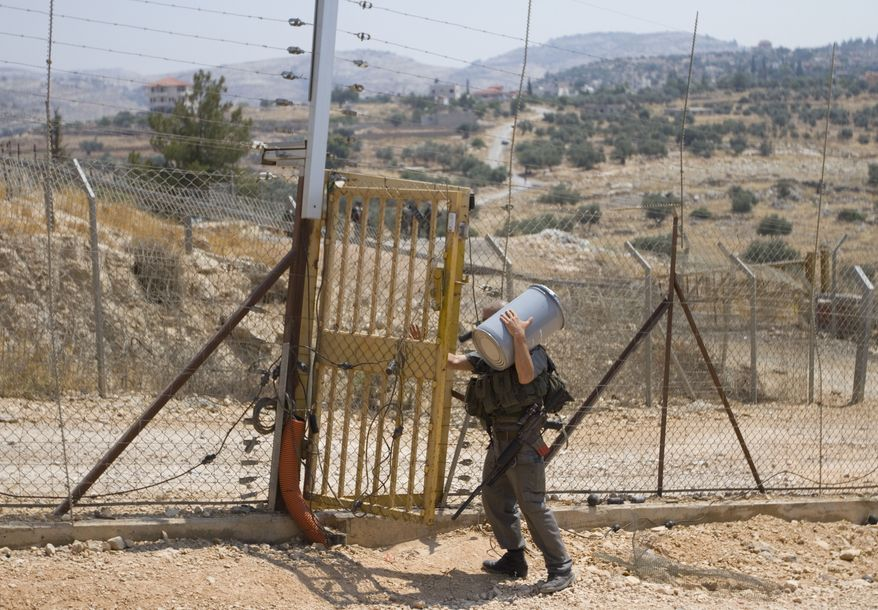An Israeli border police officer carries a canister with tear-gas grenades as he crosses between fences in Israel's separation barrier between the outskirts of the West Bank village of Bilin, near Ramallah, and the Israeli settlement of Modiin Illit on Sunday, June 26, 2011. (AP Photo/Ariel Schalit)