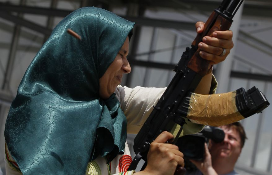 """A Libyan woman closes her eyes as she fires in the air during a graduation ceremony after a weapons training course in Tripoli, Libya, on Sunday, June 26, 2011. Government spokesman Moussa Ibrahim said Libyan officials have given out 1.2 million weapons and were training people all around territories under Col. Moammar Gadhafi's control as """"a challenge for rebels."""" (AP Photo/Ivan Sekretarev)"""