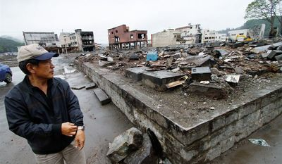 MUCH TO DO: Takaaki Goto, 74, looks at a cemetery of his ancestors in the tsunami-devastated town of Otsuchi, Japan. A town father, Mr. Goto says he is trying to recruit younger people to re-establish leadership. (Christopher Johnson/Special to The Washington Times)