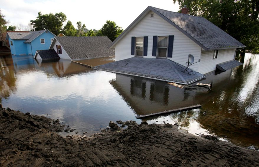 The Souris River peaked with the highest level of water on record surrounding homes on 3rd St. N.W. on Monday, June 27, 2011 in Minot, N.D. (AP Photo/Charles Rex Arbogast)