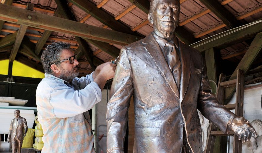 ASSOCIATED PRESS Sculptor Istvan Mate puts some finishing touches on his statue of former President Ronald Reagan, which will be unveiled in Budapest on Wednesday. The bronze statue will stand in the city's Freedom Square.