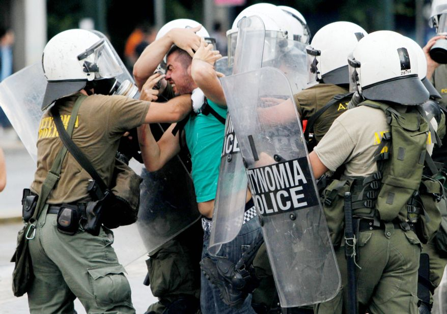 Riot police arrest a protester during a demonstration in Athens. Greece's beleaguered government is bracing for a 48-hour general strike as lawmakers debate a new round of austerity reforms designed to win the country additional rescue loans needed avoid bankruptcy. (AP Photo/Petros Karadjias)