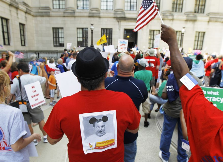 ** FILE ** Rick Rivera (center), a retired schoolteacher from Upper Freehold, N.J., sports on his back a picture of New Jersey Gov. Chris Christie with Mickey Mouse ears as Mr. Rivera and public employee union members protest near the Statehouse in Trenton, N.J., on Monday, June 20, 2011. The state Senate and Assembly were debating a bill requiring sharply higher pension and health care contributions from public employees. The governor signed the legislation on Tuesday, June 28, 2011. (AP Photo/Julio Cortez)