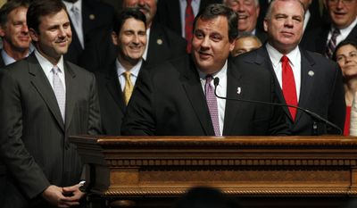 Flanked by Republican New Jersey state Sen. Thomas H. Kean (left) and Democratic state Senate President Stephen M. Sweeney (right), New Jersey Gov. Chris Christie answers a question after signing public employee benefits legislation into law on Tuesday, June 28, 2011, in Trenton, N.J. (AP Photo/Mel Evans)