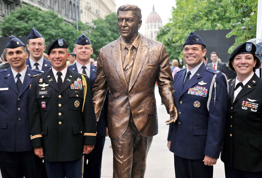 Associated Press photographs U.S. Air Force and Army officers serving in Hungary pose with the new statue of former President Ronald Reagan in Budapest on Wednesday. The 7-foot-2 bronze statue honors Reagan for his efforts to free Hungary from the yoke of communism.