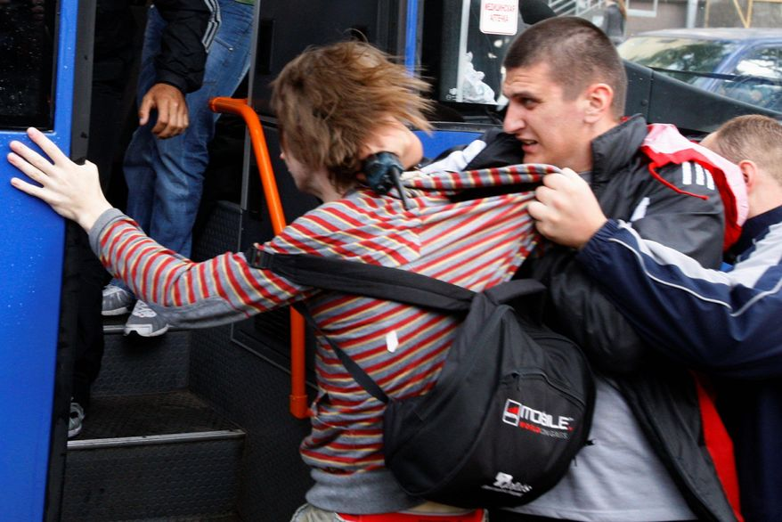 """ASSOCIATED PRESS Belarus plainclothes policemen detain a protester during a """"Revolution by Social Networks"""" rally in Minsk on Wednesday. The Vesna rights advocacy group said more than 100 people were arrested after police lost patience and began rounding up the demonstrators, beating many with truncheons."""