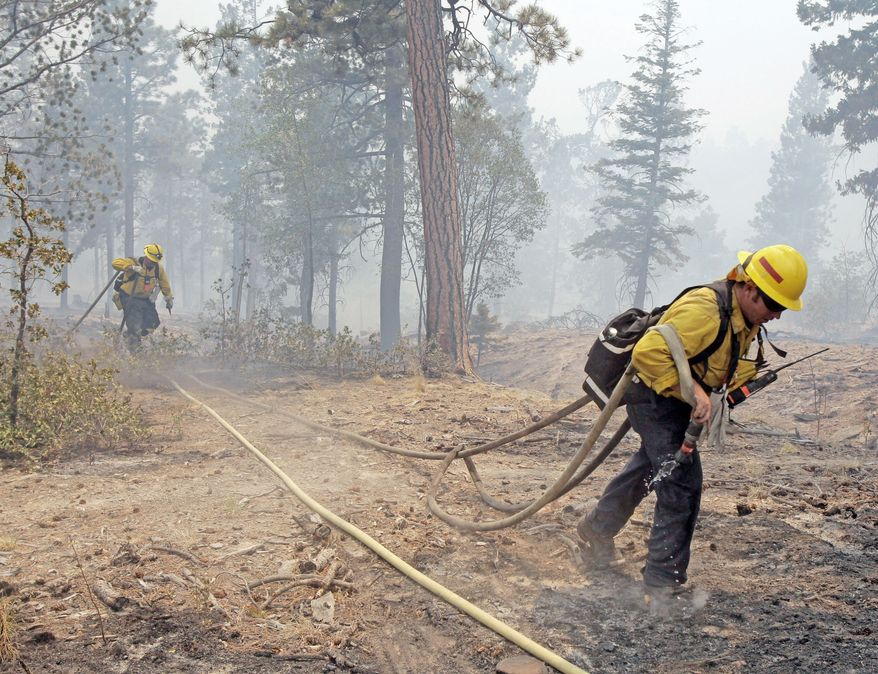 ASSOCIATED PRESS Firefighters from Apple Valley, Calif., battle the Las Conchas fire near Los Alamos, N.M., on Wednesday. The blaze had grown to more than 108 square miles by Wednesday morning, but it was being held back from the southern boundary of the Los Alamos National Laboratory and its above-ground storage area.