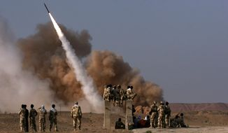 **FILE** Iranian Revolutionary Guard personnel watch the launch of a Zelzal missile during military maneuvers near Qom on June 28, 2011. (Mehr News Agency via Associated Press)