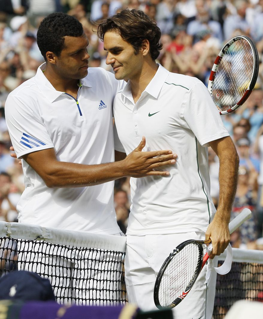 France's Jo-Wilfried Tsonga (left), consoles Switzerland's Roger Federer after defeating him in their match at the All England Lawn Tennis Championships at Wimbledon on June 29, 2011. (Associated Press)