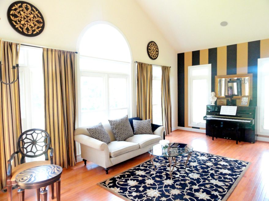 The current owner keeps a piano in the Florida room, which has a large Palladian window and a striped accent wall.