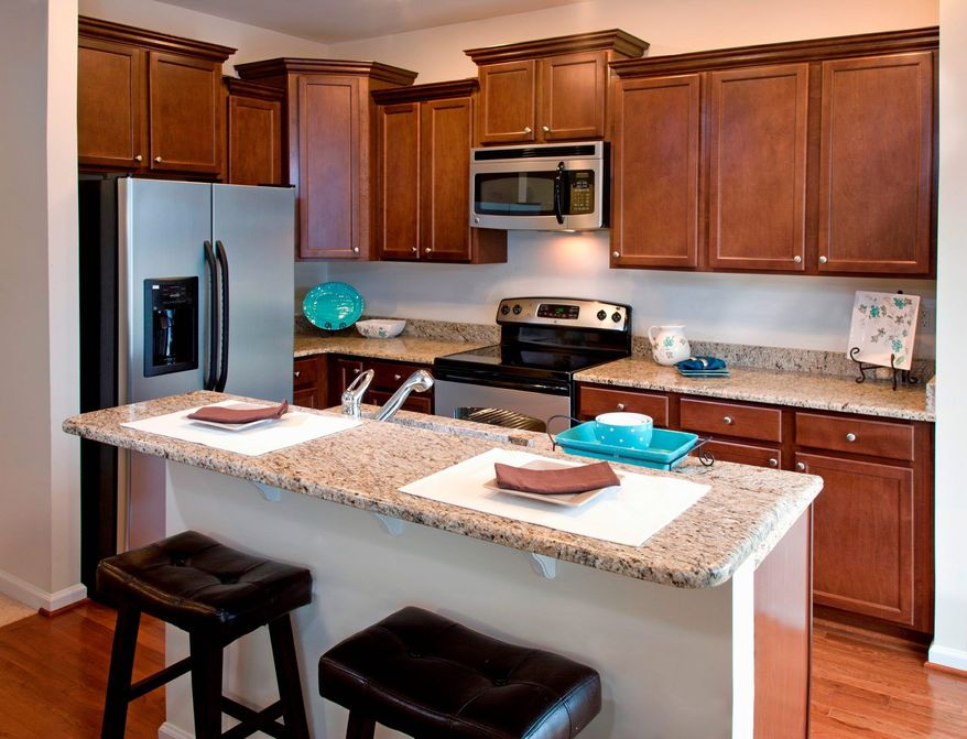 The center-island kitchen in the Kentwell model is open to the breakfast area. The kitchen has granite counters and oak cabinets.