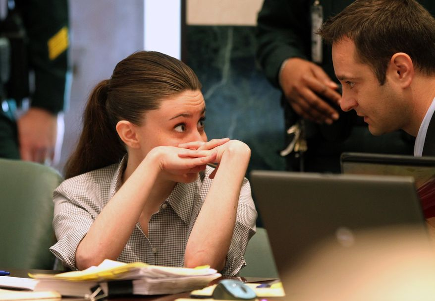 Casey Anthony talks to an unidentified man during her murder trial at the Orange County Courthouse Thursday, June 30, 2011, in Orlando, Fla. Anthony, 25, has plead not guilty in the death of her daughter, Caylee, and could face the death penalty if convicted of that charge. (AP Photo/Red Huber, Pool)