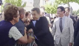 In this image made from television, a man's hand is seen on the shoulder of French President Nicolas Sarkozy as the president shakes hands with a crowd in Brax, France, on June 30, 2011. A man in a crowd grabbed Sarkozy by the shoulder and nearly knocked him to the ground before being tackled by security officers and detained. (Associated Press/French pool)