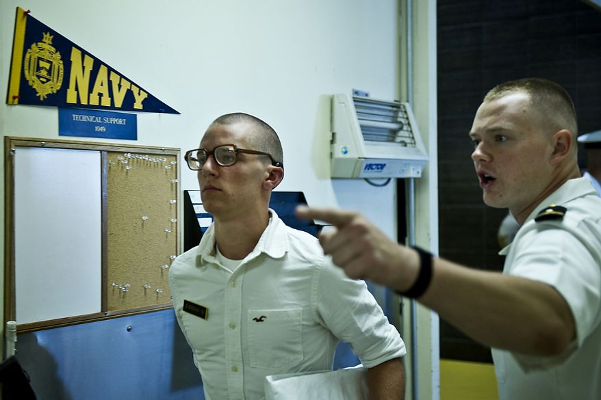 """Midshipman 1/C Matthews Adams (right), a fourth-year student at the U.S. Naval Academy, instructs Ian Eversman, a plebe from Kingsland, Ga., to """"walk fast and with purpose"""" as he makes his way from getting his hair cut to picking up his gear during Induction Day at the academy in Annapolis on Thursday, June 30, 2011. It is tradition for plebes to be yelled on their walk. (Drew Angerer/The Washington Times)"""