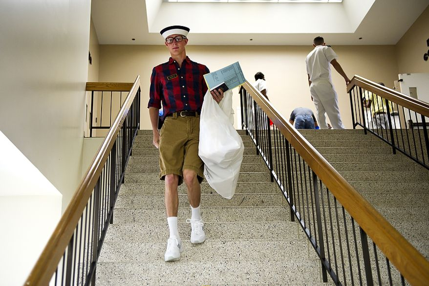 Blake Nixon, a plebe from Austin, Tex., makes his way down the stairs in Alumni Hall after registering and picking up his Navy-issued clothes and gear during Induction Day at the U.S. Naval Academy in Annapolis on Thursday, June 30, 2011. (Drew Angerer/The Washington Times)