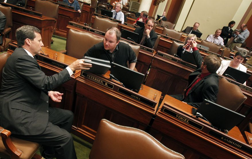 Rep. Keith Downey (left) talks to Rep. Branden Petersen on the house floor on June 30, 2011, as they await the government shutdown in the capitol in St. Paul, Minn. The Minnesota state government shutdown at 12:01 a.m. CDT on July 1, 2011. (Associated Press/Carlos Gonzalez/Star Tribune)