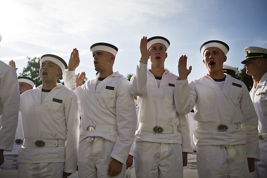 Incoming Naval Academy Plebes raise their hand as they take Oath of Office, in Tecumseh Court, the courtyard of Bancroft Hall, on Induction Day at the U.S. Naval Academy, in Annapolis, Md., Thursday, June 30, 2011. Induction Day marks the day the young men and women begin their transformation from civilians to midshipmen and begin their Plebe Summer training program. (Drew Angerer/The Washington Times)