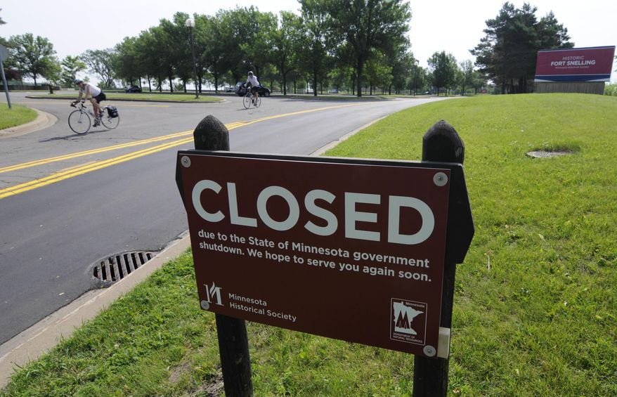 A bicyclist rides on the road leading out of the closed Fort Snelling historic site Friday, July 1, 2011, in Minneapolis after negotiations over the state budget between Republican lawmakers and Democratic Gov. Mark Dayton broke down and the government shutdown at midnight. AP Photo/Jim Mone)