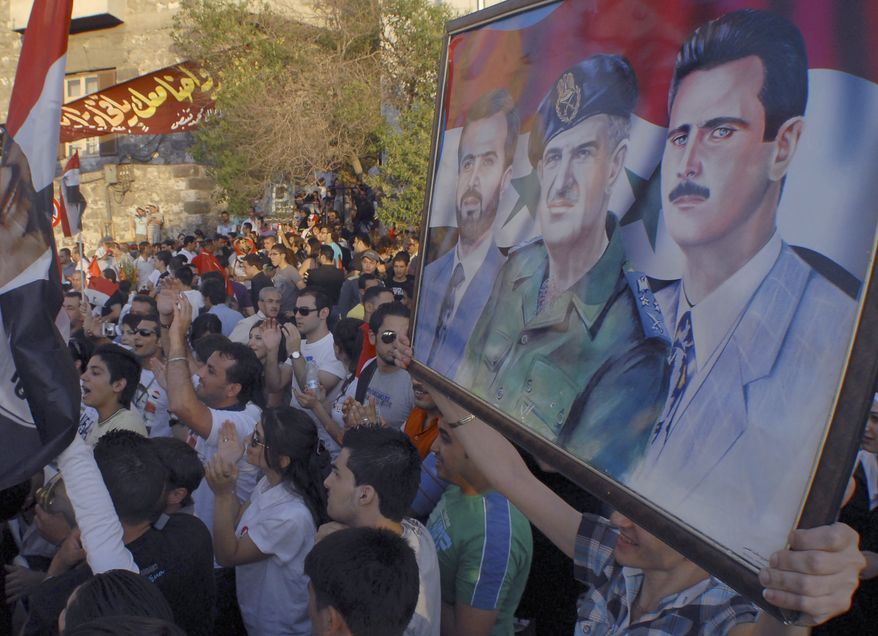 Pro-Syrian President Bashar Assad protesters hold up a poster of him (shown far right) during a demonstration to show their support in Damascus, Syria, on Friday, July 1, 2011. Hundreds of thousands of protesters flooded cities around Syria on Friday in one of the largest outpourings against the regime of Assad. (AP Photo/Muzaffar Salman)