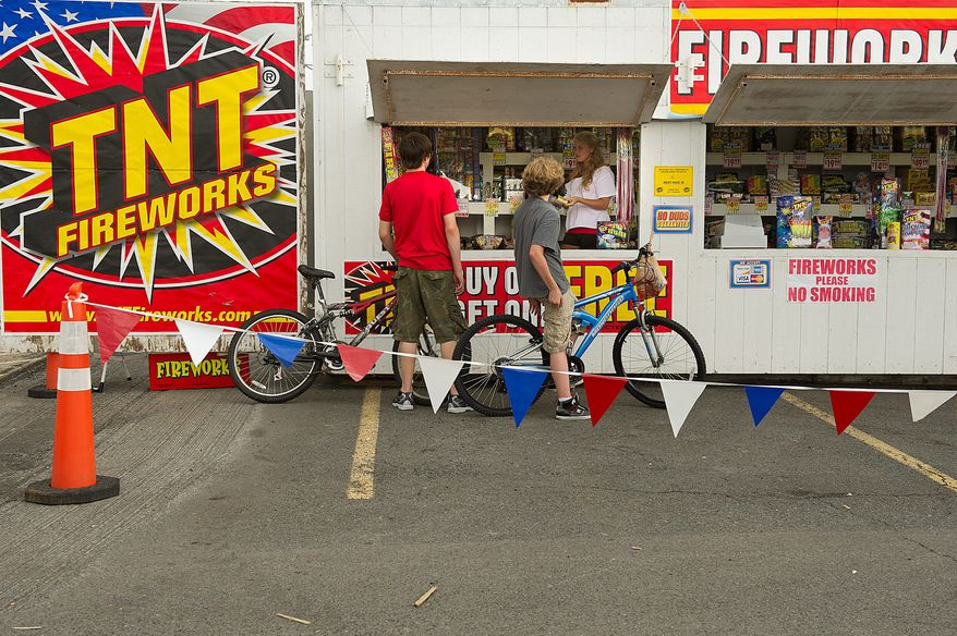 PHOTOGRAPHS BY BARBARA L. SALISBURY/THE WASHINGTON TIMES Two boys ask questions about the fireworks for sale at the TNT fireworks booth in Manassas, Va. They were turned away because they weren't yet 16 years old, the minimum age to buy fireworks.