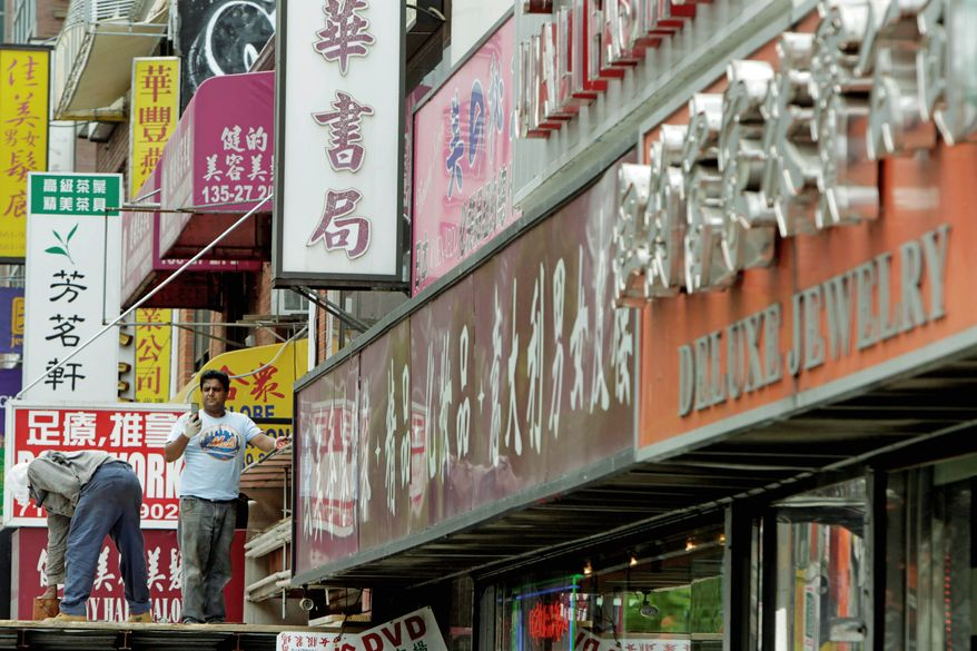 Signs primarily in languages other than English are displayed in the Flushing, Queens, section of New York City. City Council members are wading into a potential culture clash with a bill that would require 60 percent of a business's exterior signage to be in English. (Associated Press)