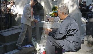** FILE ** Two former members of the Doors, keyboardist Ray Manzarek (right) and guitarist Robby Krieger, light candles at the grave of Jim Morrison at the Pere Lachaise Cemetery in Paris on Sunday, July 3, 2011. Morrison, the legendary lead singer of the rock band, died in Paris on July 2, 1971. (AP Photo/Jacques Brinon)